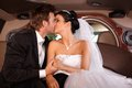 Bride and groom kissing in limo limousine on wedding day Royalty Free Stock Photo