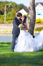 Bride and groom kissing at park against river view Stock Image