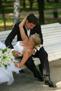 Bride and Groom Kissing on Park Bench Royalty Free Stock Image