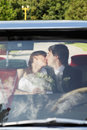 Bride and groom kissing while sitting in the car Royalty Free Stock Image