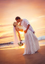 Bride and groom kissing at sunset on a beautiful tropical beach romantic married couple Royalty Free Stock Photography