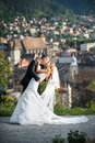Bride and groom kissing with the town in the background Stock Images