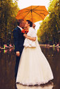 Bride and groom kissing under umbrella in park Royalty Free Stock Photos