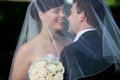Bride and groom kissing under veil holding flower bouquet in hand Stock Photo