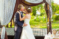 Bride and groom kissing under wedding arch Royalty Free Stock Photo