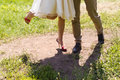 Bride and groom legs standing on the green grass Stock Image