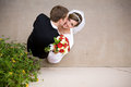 Bride and groom morman with bouquet looks up on her wedding day Royalty Free Stock Image