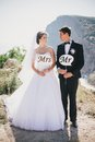Bride and groom with mr and mrs signs just married beautiful young standing on the mountains background Stock Photos