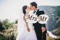 Bride and groom with mr and mrs signs just married beautiful young standing on the mountains background Royalty Free Stock Photography