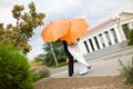 Bride and groom with orange umbrellas Stock Photography