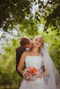 Bride and groom in a park kissing couple newlyweds bride and groom at a wedding in nature green forest are kissing photo portrait Stock Image