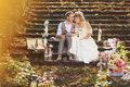 The bride and groom in retro style hugging on stone steps at autumn forest, surrounded by wedding decor. Royalty Free Stock Photo