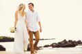 Bride and groom romantic newly married couple holding hands wal walking on the beach just Stock Photo