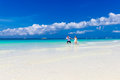 The bride and groom running on a tropical beach having fun Stock Photo