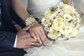 Bride and groom s hands with wedding rings bouquet of flowers Stock Images