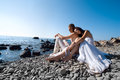 Bride and groom on sea coast are sitting rocks the Stock Photos