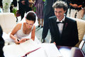 Bride and groom signing registry Royalty Free Stock Photo