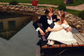 The bride and groom sit on dock Stock Image