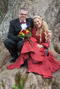 Bride and groom sitting in front of a tree are arm arm she wears red wedding dress Stock Images