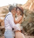 Bride and groom stand, hug and smile in canyon against background of rocks. Closeup. Royalty Free Stock Photo