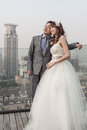 Bride and groom standing  ouside with shanghai jingguang waitan Stock Photo