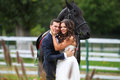 Bride and groom at stud black horse Royalty Free Stock Photo