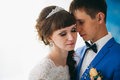 Bride and groom in studio light stand kiss on a white background Royalty Free Stock Photo