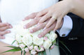 Bride and groom with their hands on the bride s bouquet concept Stock Image