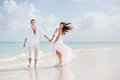 Bride and groom on the tropical beach walking along a Stock Photography