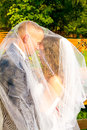 Bride and groom under veil bridal covers the on their wedding day while they share a special moment together for a portrait of Royalty Free Stock Photography