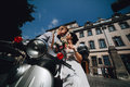 Bride and groom on vintage motor scooter posing a Stock Photos