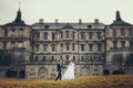 Bride and groom walk along the yellow lawn in the front of an ol Royalty Free Stock Photo