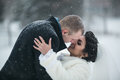 Bride and groom walking on the European city in the snow Royalty Free Stock Photo