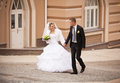 Bride and groom walking on paving road at old city young Stock Photography