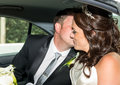 Bride and groom in wedding car kissing the after the ceremony Royalty Free Stock Photography