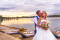 Bride and groom wedding in pier with boats on lake Royalty Free Stock Photo