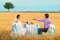 Bride and groom on the wheat field next to wedding table Stock Photography