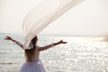 Bride with her arms raised standing near waterline Stock Photo