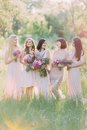 Bride with her bridesmaids are laughting and holding the bouquets of the pink flowers in the green sunny forest. Royalty Free Stock Photo