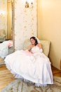 The bride in her wedding dress is sitting in his chair and smiles Stock Photos