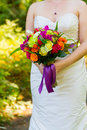 Bride holding bouquet flowers a in a white wedding dress holds her of on her wedding day Stock Photo