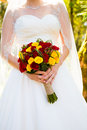 Bride holding bouquet flowers a in a white wedding dress holds her of on her wedding day Royalty Free Stock Image