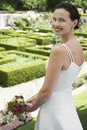 Bride holding bouquet in formal garden portrait of beautiful young Stock Photography