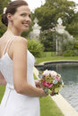 Bride holding bouquet at poolside beautiful young Royalty Free Stock Images