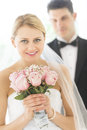 Bride holding flower bouquet with groom standing in background portrait of beautiful young Stock Images