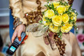 Bride holding flower and handphone view of a folding a bouquet of yellow roses a Stock Images