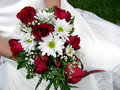 Bride holding her wedding bouquet against her dress Royalty Free Stock Photos