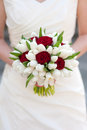 Bride holding red rose and white tulip wedding bouquet Royalty Free Stock Photo