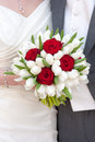 Bride holding red rose and white tulip wedding bouquet Stock Image