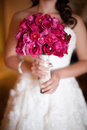Bride holding rose bouquet a in a wedding dress a red and pink of roses Stock Photos